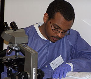 Student with microscope writing