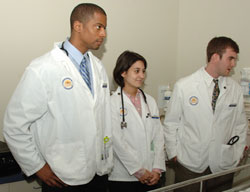 Three med students at patient bedside