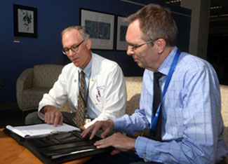 Drs. Regenold and Robinson reviewing a day planner