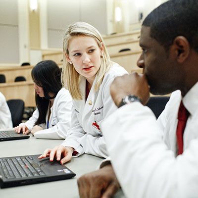 Two students wearing white lab coats in class with laptops