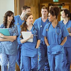 Group of medical students wearing scrubs walking