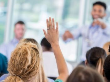 medical student raising hand and presenter pointing