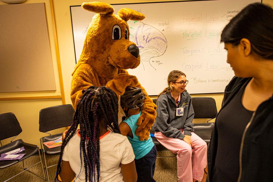 Dog mascot hugging child in classroom