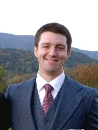 Photo of Collin Brinkman in a navy suit with white shirt and red tie. There are mountains and trees in the background.