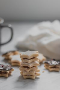 A stack of star shaped sugar cookies on a marble countertop with the handle of a mug and some frosting in the background