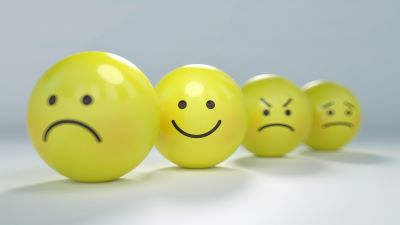 Four yellow balls with black faces drawn on them in marker. The front face is a frown, the second face is a smile, the third face is angry, and the fourth face is worried.