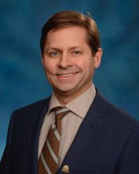 Dr. Todd Gould in a black suit with brown shirt and tie against a blue background