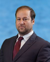 Photo of Dr. James Borrelli in a black suit jacket, white shirt, and red tie on a blue background