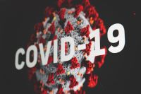 Photo of Covid molecule with COVID-19 in white text across it