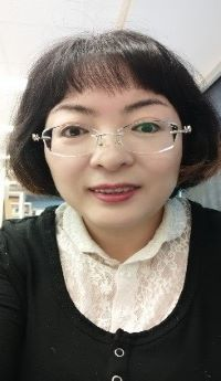 Photo of Hongxia Chen wearing a black cardigan with white lace blouse