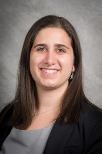 Cali Calarco, PhD in black blazer and gray top against a gray background