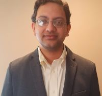 Photo of Parikshit Moitra, PhD in a grey suit jacket and white shirt against a beige background