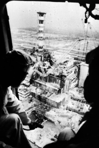Silhouettes of two men looking down at the Chernobyl plant from a helicopter.