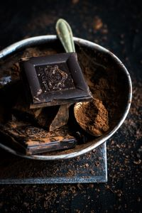 A square of chocolate in a metal bowl full of cocoa powder and a silver spoon. The background is black with more sprinkled cocoa powder.