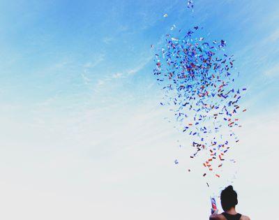 Person shooting confetti into blue sky