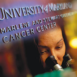 Scientist looking into microscope with UM Greenebaum Cancer Center logo on top of graphic
