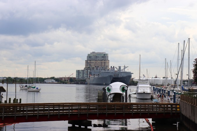 Mrs Trashwheel,a bridge, military ships, sailboats in the Inner Harbor, and Silo Point apartment building in background